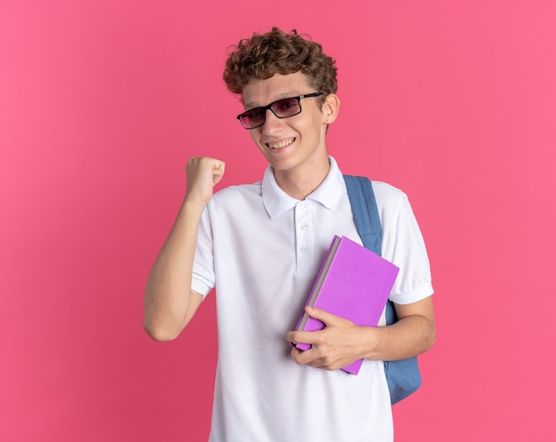Ragazzo studente in abbigliamento casual con gli occhiali con lo zaino che tiene il pugno serrato del taccuino