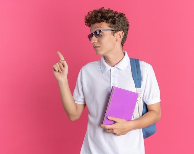 Studente in abbigliamento casual con gli occhiali con zaino in mano il taccuino