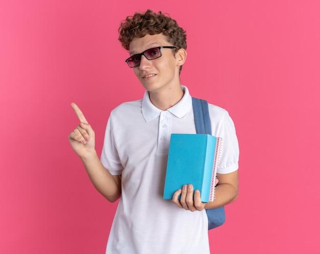 Ragazzo studente in abbigliamento casual con gli occhiali con lo zaino che tiene i quaderni guardando la telecamera