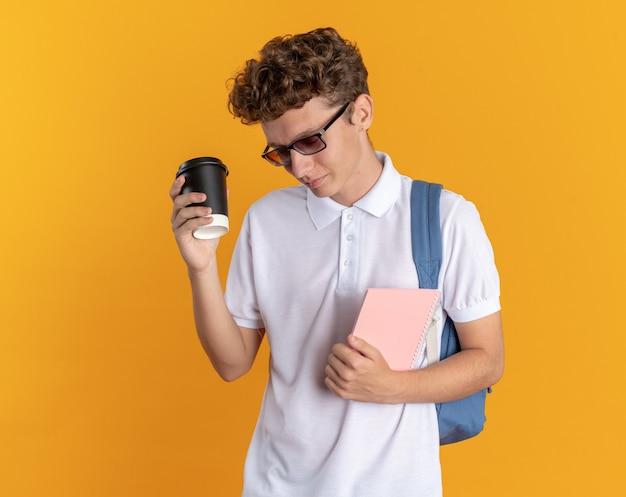 Ragazzo studente in abbigliamento casual con gli occhiali con lo zaino che tiene un bicchiere di carta