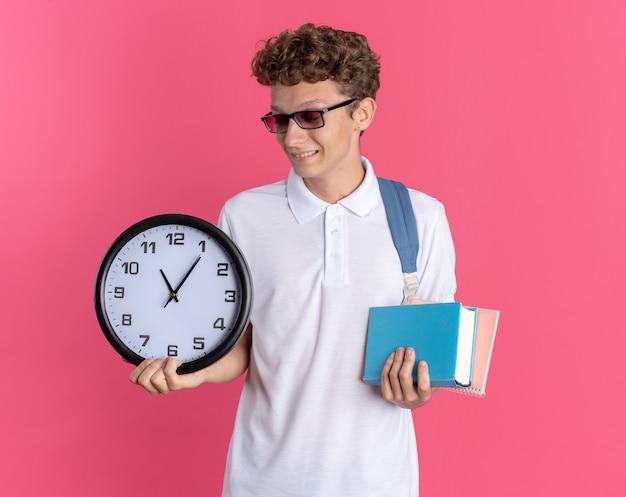 Ragazzo studente in abbigliamento casual con gli occhiali con lo zaino che tiene l'orologio da parete e i quaderni sorridenti