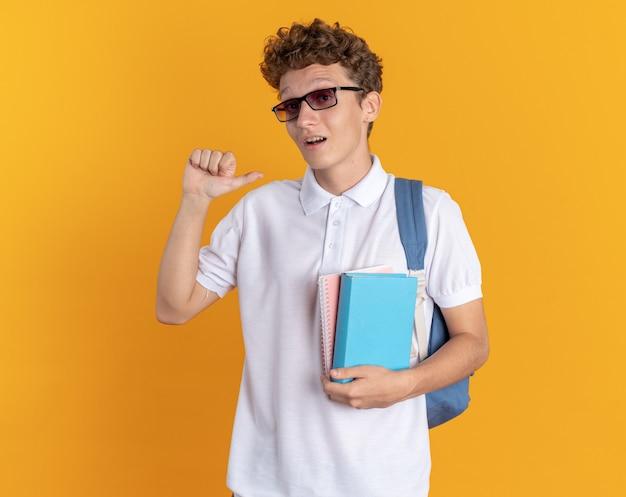 Ragazzo studente in abbigliamento casual con cuffie che indossa occhiali con zaino con libri