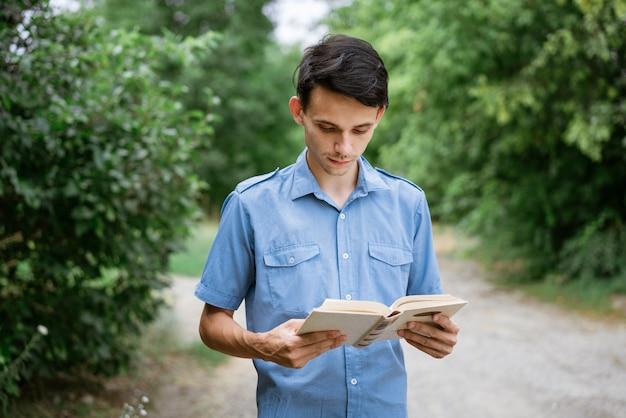 공원에서 그의 손에 책을 파란색 셔츠에 학생 남자가 읽습니다.