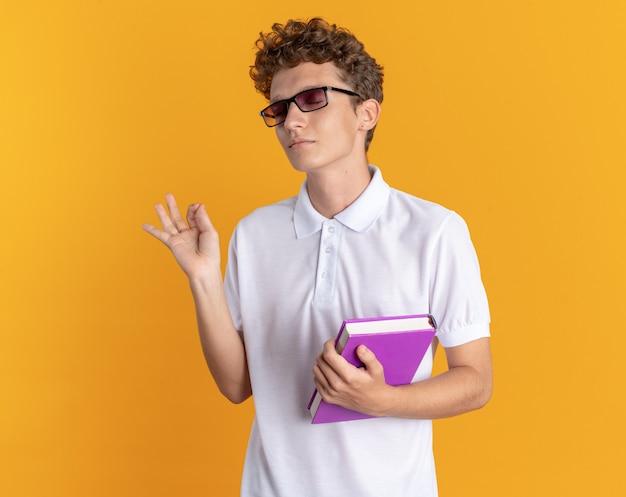 オレンジ色の背景の上に立っているokのサインを見せて幸せで喜んでカメラを見て本を持って眼鏡をかけているカジュアルな服を着た学生の男