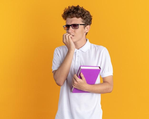 オレンジ色の背景の上に立っているカメラのストレスと神経質な噛む爪を見て本を保持している眼鏡をかけているカジュアルな服を着た学生の男