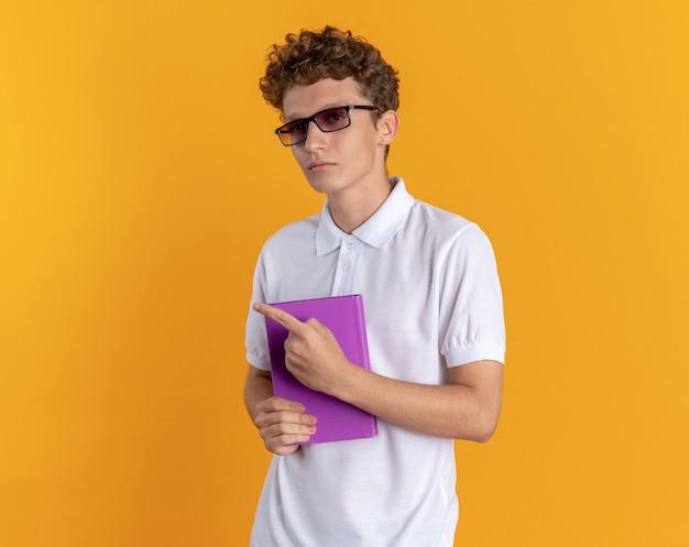 オレンジ色の背景の上に立っている側に指で指している真面目な顔でカメラを見て本を持って眼鏡をかけているカジュアルな服を着た学生男