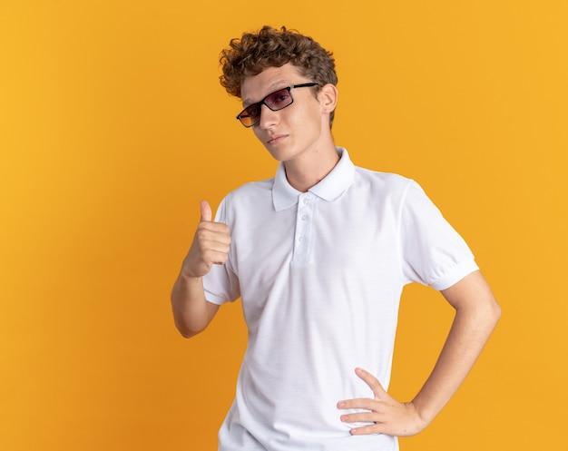 笑顔で親指を示す眼鏡をかけているカジュアルな服を着た学生の男
