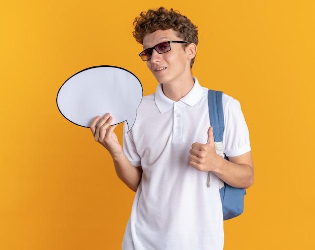 안경을 쓰고 배낭을 메고 빈 말풍선이 있는 안경을 쓴 학생 남자는 주황색 배경 위에 자신감 있게 서 있는 엄지손가락을 보여주는 카메라를 보고 있습니다.