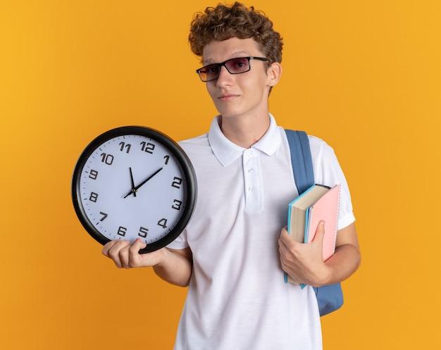 オレンジ色の背景の上に立っている顔に自信を持って笑顔でカメラを見て本と壁時計を保持しているバックパックと眼鏡をかけてカジュアルな服を着た学生男