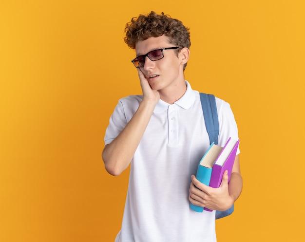 Студент парень в повседневной одежде в очках с рюкзаком держит книги, выглядя усталыми и скучающими, с рукой на лице, стоящей на оранжевом фоне