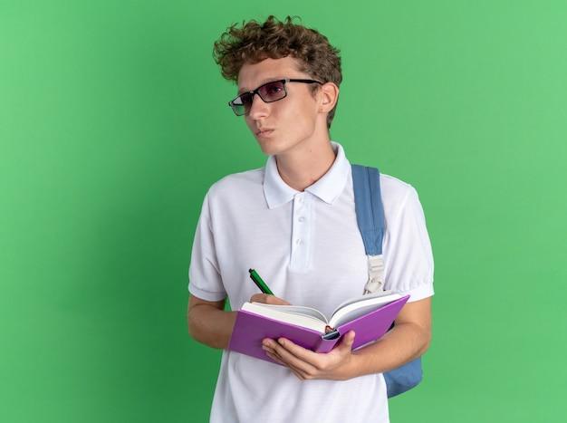 Парень-студент в повседневной одежде в очках с рюкзаком, держащим блокнот и ручкой, что-то пишет с серьезным лицом