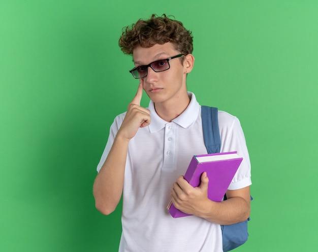 녹색 배경 위에 서 있는 검지 손가락으로 자신의 눈을 가리키는 카메라를 바라보는 노트북을 들고 배낭을 메고 안경을 쓴 캐주얼 옷을 입은 학생