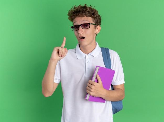 緑の背景の上に立って幸せで興奮している新しいアイデアを持っている人差し指を示すノートブックを保持しているバックパックと眼鏡をかけてカジュアルな服を着た学生の男