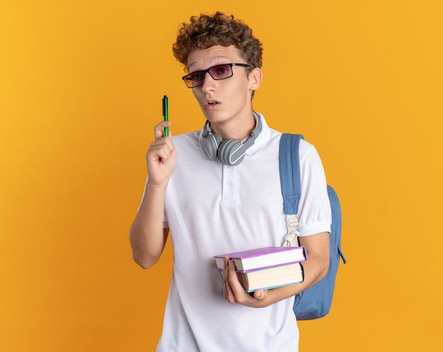 オレンジ色の背景の上に立っている新しいアイデアを持って驚いたように見えるバックパックと本とペンを保持している眼鏡をかけているヘッドフォンでカジュアルな服を着た学生の男