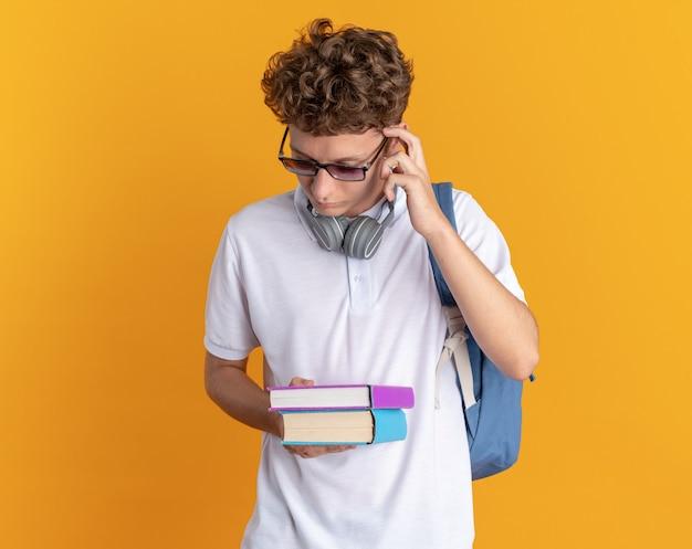 책을 들고 배낭과 안경을 쓰고 헤드폰으로 캐주얼 의류에 학생 남자