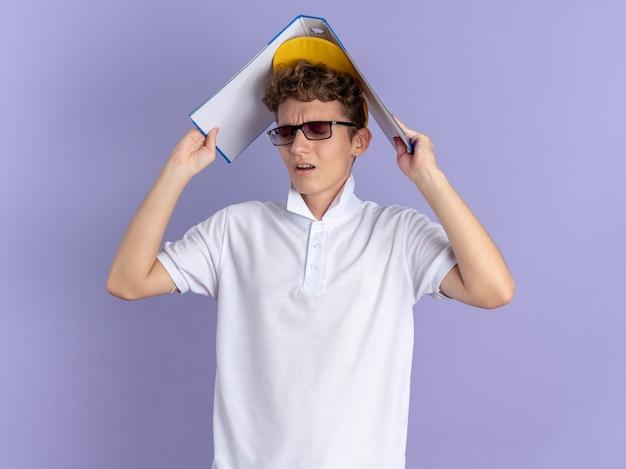 Студент парень в белой рубашке поло и желтой кепке в очках держит папку