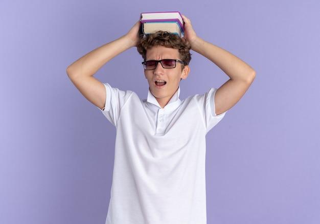 白いポロシャツと黄色い帽子をかぶった学生の男は、青い背景の上に立ってイライラして疲れているように見える彼の頭の上にノートを保持している眼鏡をかけています