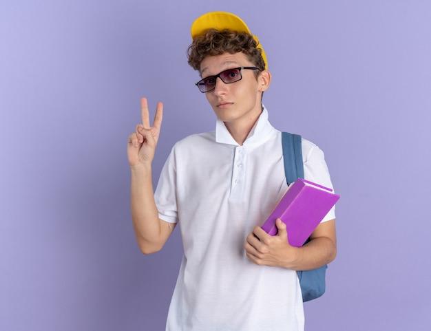 白いポロシャツと黄色の帽子をかぶった学生の男は、青い背景の上に立っているvサインを示す深刻な顔でカメラを見てノートブックを保持しているバックパックと眼鏡をかけています