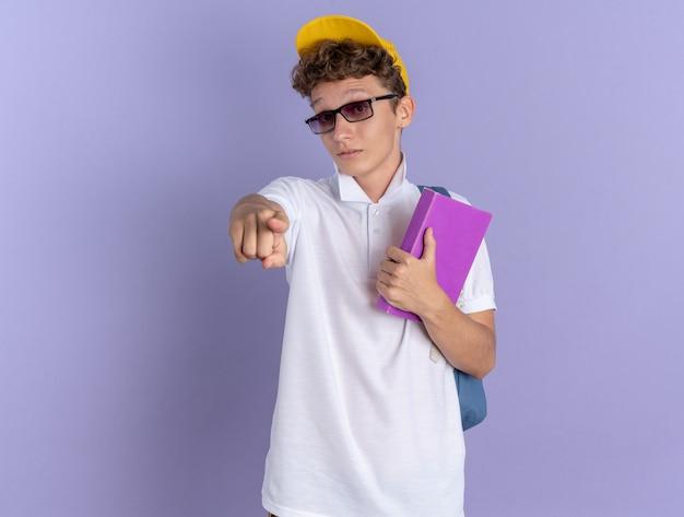 白いポロシャツと黄色い帽子をかぶった学生の男が驚いているカメラに人差し指で指しているノートブックを保持しているバックパックと眼鏡