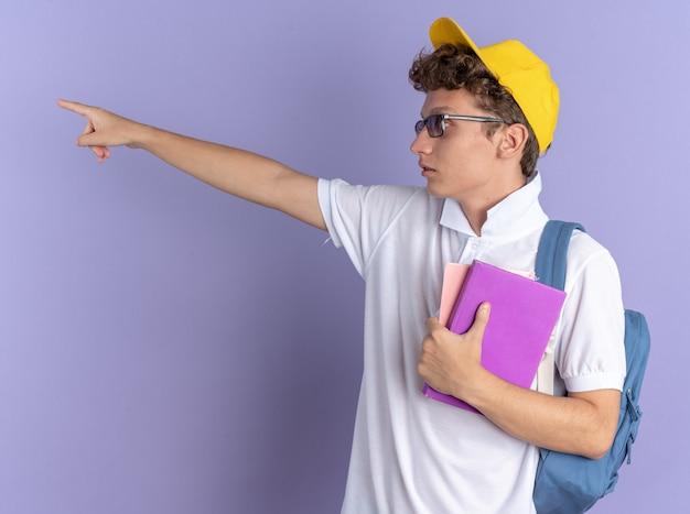 白いポロシャツと黄色い帽子をかぶった学生の男が、驚いたことに人差し指で指さして脇を向いているノートを保持しているバックパックと眼鏡をかけています
