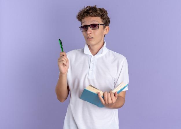 本とペンを持って眼鏡をかけている白いポロシャツの学生の男が青い背景の上に立っている新しいアイデアを持って驚いたカメラを見て