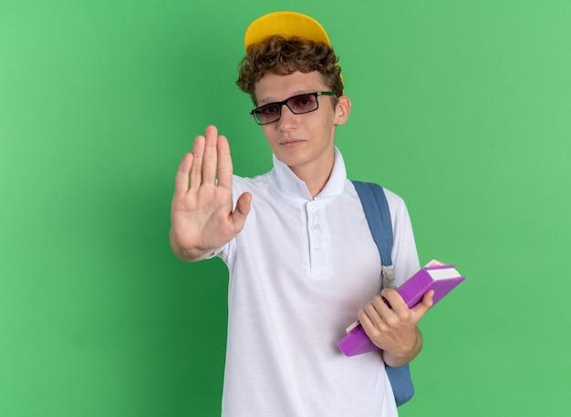 Студент в белой рубашке и желтой кепке в очках с рюкзаком держит ноутбуки, глядя в камеру с серьезным лицом, делая жест рукой