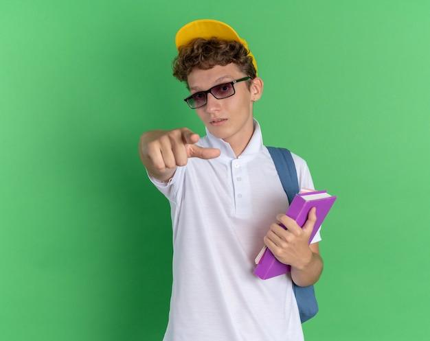 자신감을 찾고 카메라에 검지 손가락으로 가리키는 노트북을 들고 배낭과 안경을 쓰고 흰 셔츠와 노란 모자에 학생 남자