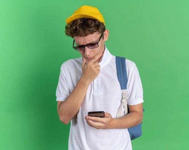 Студент в белой рубашке и желтой кепке в очках с рюкзаком, держащим смартфон, озадаченно глядя на него, стоя на зеленом фоне