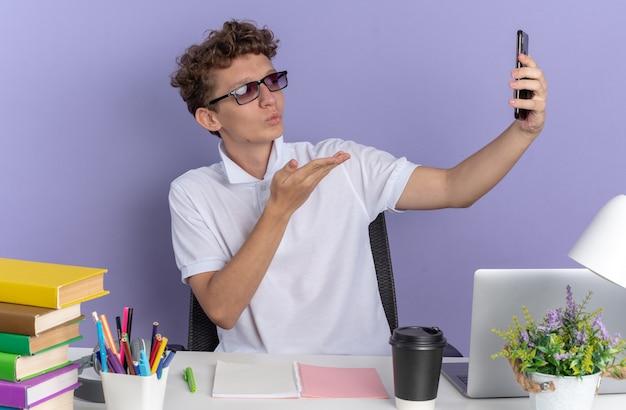 Ragazzo studente in polo bianca con gli occhiali seduto al tavolo con libri in possesso di smartphone con videochiamata che soffia un bacio su sfondo blu