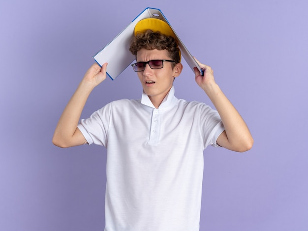 Student guy in white polo shirt and yellow cap wearing glasses holding folder