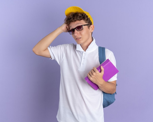 Student guy in white polo shirt and yellow cap wearing glasses with backpack holding notebooks looking at camera confused scratching head standing over blue background