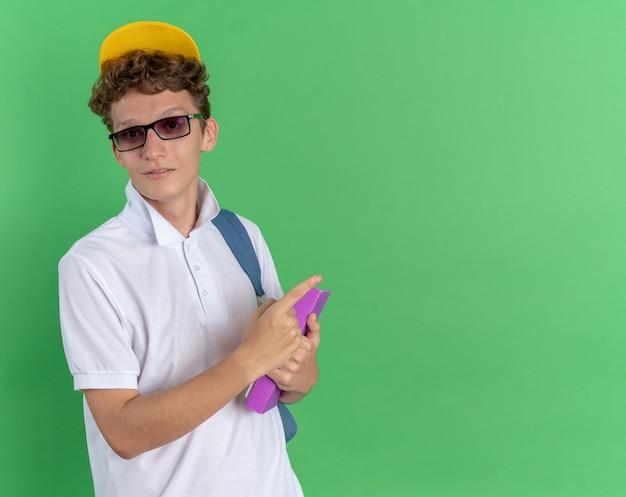 Ragazzo studente in camicia bianca e berretto giallo con gli occhiali con zaino che tiene il taccuino guardando la macchina fotografica sorridente fiducioso che punta con il dito indice allo spazio della copia in piedi su sfondo verde