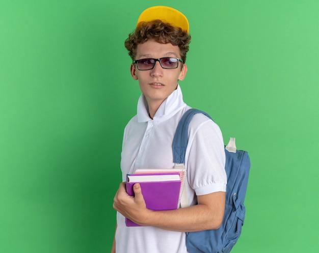 Studente in camicia bianca e berretto giallo con gli occhiali con lo zaino che tiene i taccuini espressione sicura che guarda da parte con