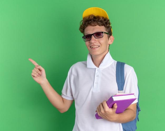 Ragazzo studente in camicia bianca e berretto giallo con gli occhiali con zaino in possesso di quaderni guardando la telecamera sorridendo allegramente puntando con il dito indice a lato
