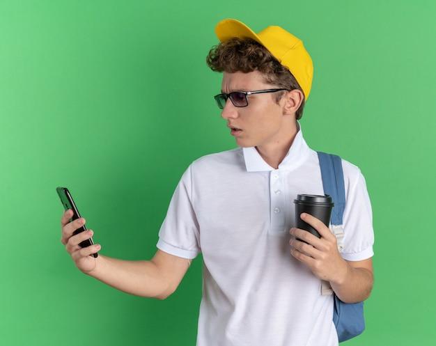 Ragazzo studente in camicia bianca e berretto giallo con gli occhiali con lo zaino che tiene lo smartphone e il bicchiere di carta che sembra confuso e dispiaciuto