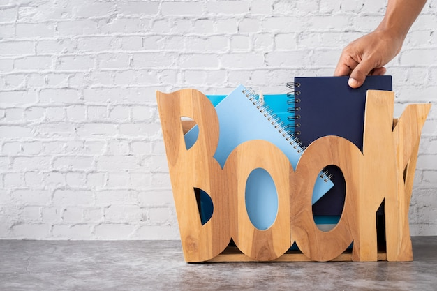 Student hand choosing and picking off book from wooden box on brick wall