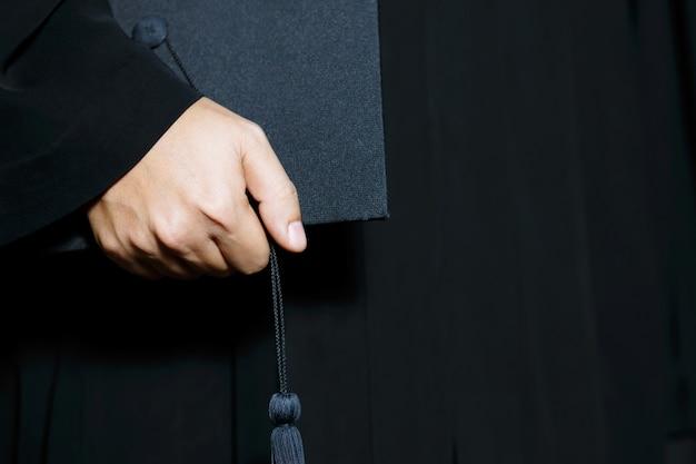 卒業帽子を持っている学生の手