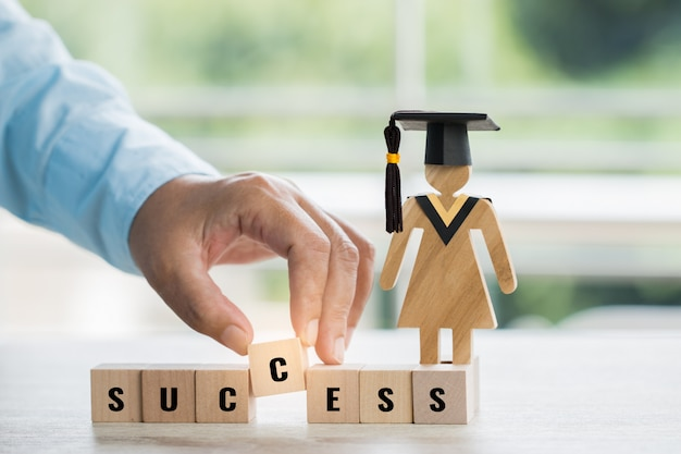 Student hand placing wooden block with letter success near sign wood with graduation