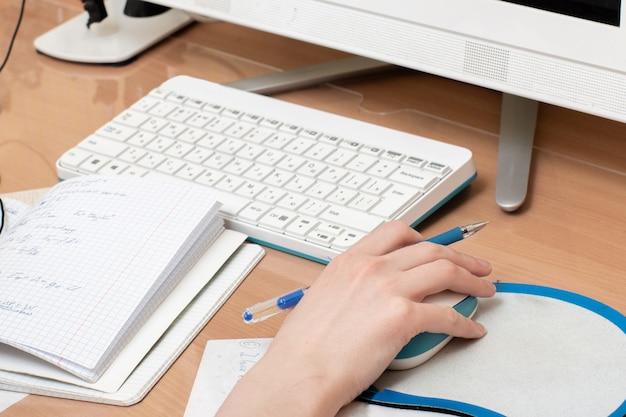 Рука студента с мышью и компьютерной клавиатурой с блокнотом и ручкой.