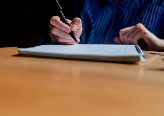 Студент руки крупным планом писать ручкой в блокноте или планировщик, делая заметки на деревянном офисном столе с ...