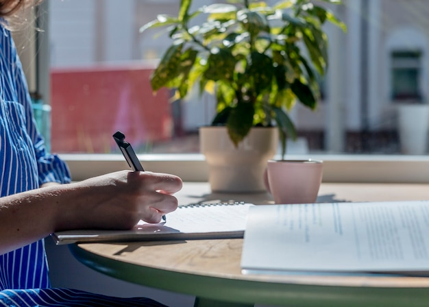 Руки студента крупным планом писать ручкой в блокноте, делая заметки, изучая учебник в современном кафе ...