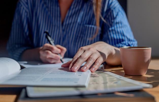 Студент руки крупным планом писать ручкой в блокноте, делая заметки из книги, изучая учебник в c ...