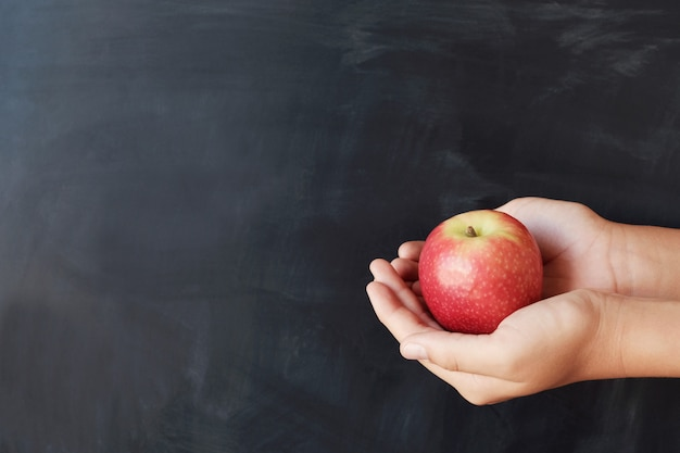 Student hands holding red apple with blackboard background