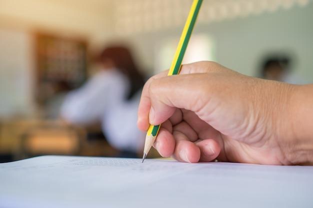 Руки студента взяв и держа карандаш для сдачи экзамена в старшей школе