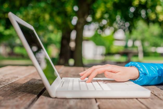 노트북과 학생 손입니다. 노트북을 사용하여 공원에서 휴식. 야외 사무실 개념을 닫습니다 비즈니스 우먼 작업, 웹 검색, 정보 브라우징을 사용 하여 노트북입니다.