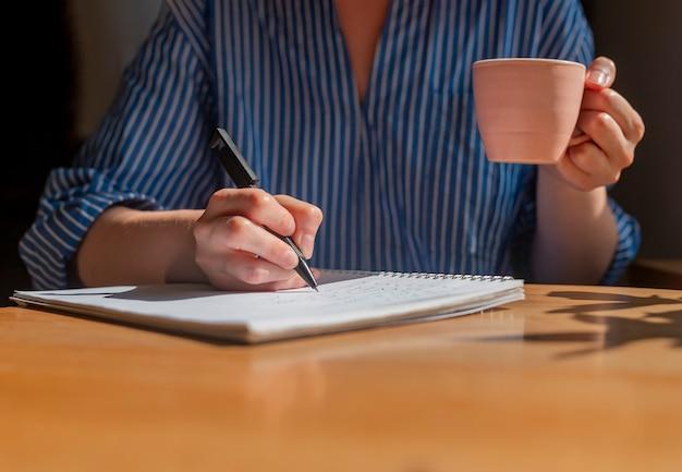 Студент руки пишет ручкой в блокноте, делая заметки и держа в руках чашку кофе