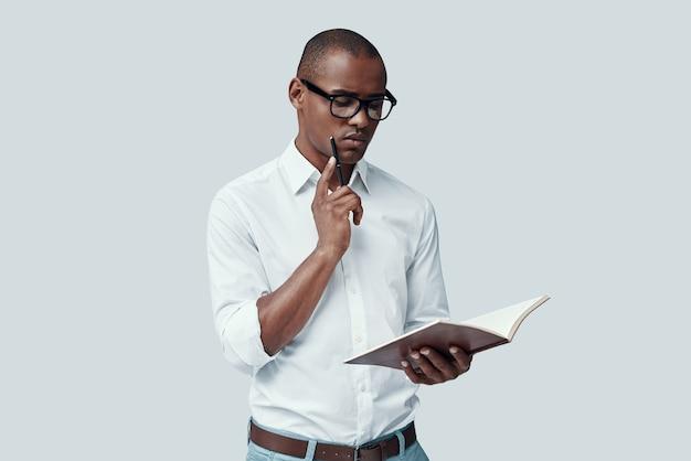 Ученик. красивый молодой африканский мужчина что-то читает, стоя на сером фоне