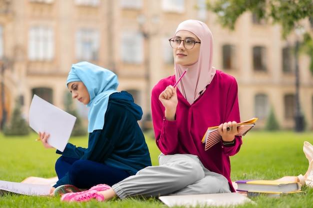 アイデアを持っている学生。プロジェクトの準備中にアイデアを持っている眼鏡をかけている美しいイスラム教徒の学生