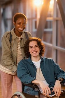 車椅子で同僚を助ける学生