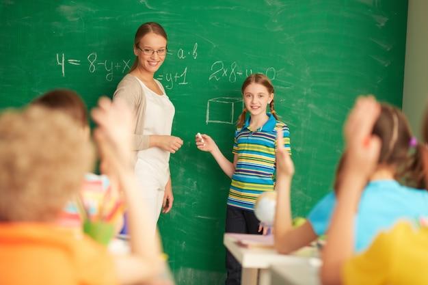 Student helping the teacher on the blackboard